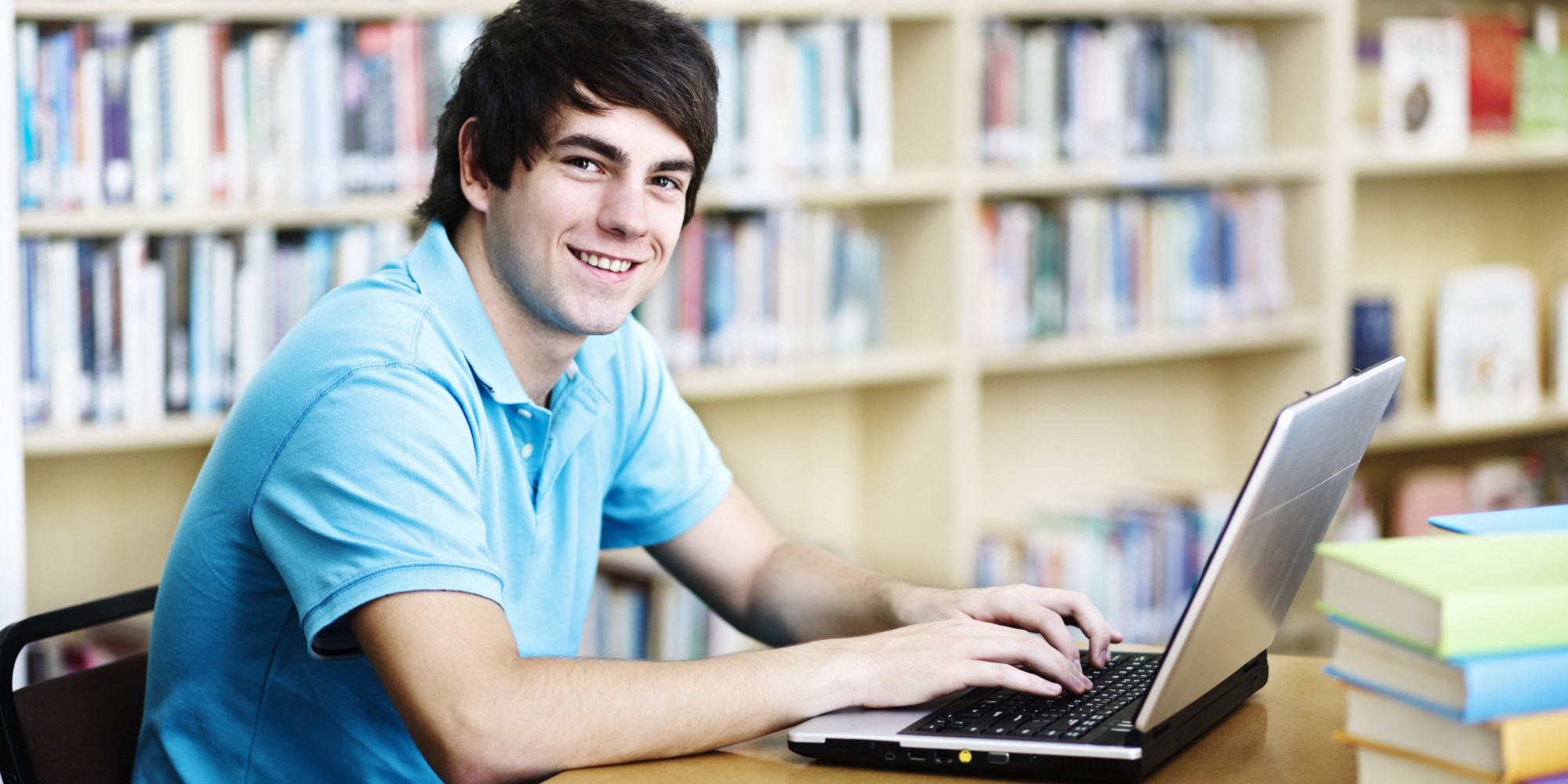 Handsome student smiles up from laptop studies in library
